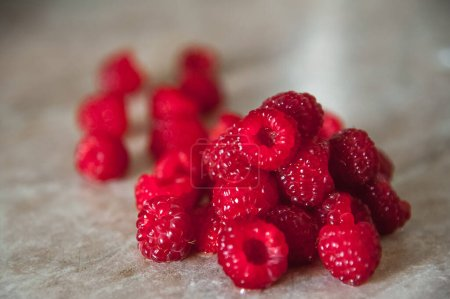 A handful of raspberries in bulk on a table with a...