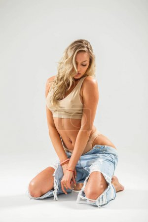 Studio portrait of beautiful blonde girl with fitness body. Woman in beige t-shirt and torn jeans posing on white background