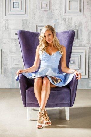 Studio portrait of beautiful blonde girl in blue dress. Sporty woman sitting in purple armchair.