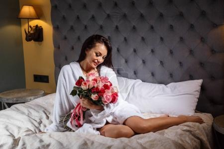 Studio portrait of beauty young brunette woman with professional makeup wearing white  bathrobe. Beautiful woman sitting on bed with pink roses bouquet, grey headboard background