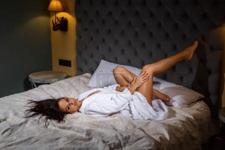 Studio portrait of beauty young brunette woman with professional makeup wearing white  bathrobe. Beautiful woman lying on bed with grey headboard
