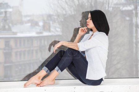 Studio shot of beautiful brunette woman wearing dark jeans and white shirt sitting on windowsill near window at apartment interior