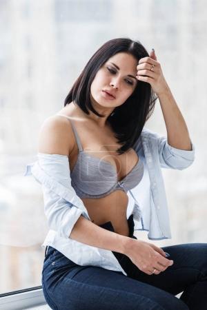 Studio shot of beautiful brunette woman wearing dark jeans and white shirt. Sexy girl in bra sitting on windowsill near window at apartment interior