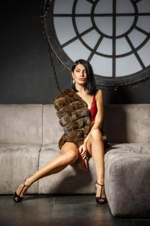 Studio portrait of beautiful brunette girl in sexy red lingerie. Shot of young woman in fur coat at apartments interior