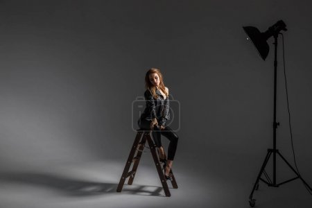 Shot of beautiful young woman wearing sexy black lingerie and black leather clothes sitting on wooden stairs at grey studio background
