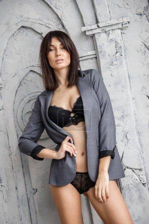 Photo pour Modèle de brune sexy en sous-vêtements et veste posant dans une pièce près du mur et de la fenêtre - image libre de droit