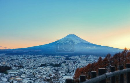 Mountain Fuji with city at sunset time.