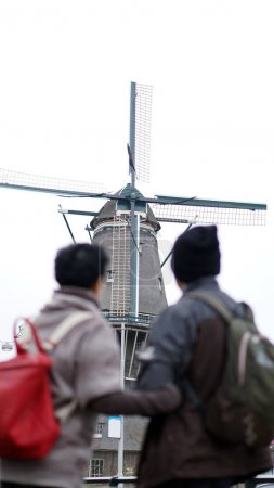 Asian senior couple anniversary trip to Netherlands windmill in