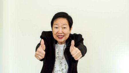 Photo for Asian senior woman wearing suit with happpy face and hand gesture - Royalty Free Image
