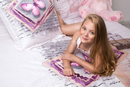 Photo for Gracious young beautiful blond girl, little princess with long hair and blue eyes, the child lies in bed, sleeping in linen in butterflies and joyfully smiles - Royalty Free Image