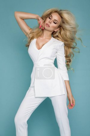 Beautiful female model in elegant clothes on a blue background