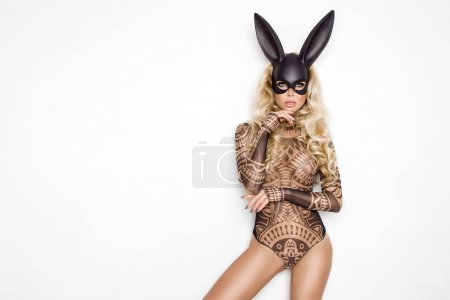 Photo for Beautiful young woman in Halloween, tattoo costume and black bunny  mask, standing on white background - Royalty Free Image