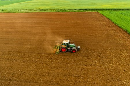 Photo for Aerial shot of  Farmer with a tractor on the agricultural field sowing. tractors working on the agricultural field in spring. Cotton seed - Royalty Free Image