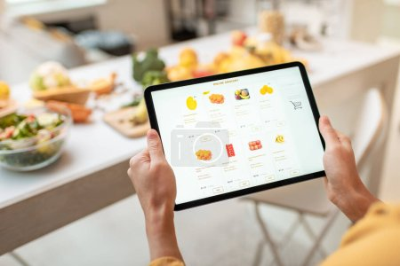 Photo for Woman shopping food online using a digital tablet at the kitchen, close-up view on a tablet screen. Concept of buying online using mobile devices - Royalty Free Image
