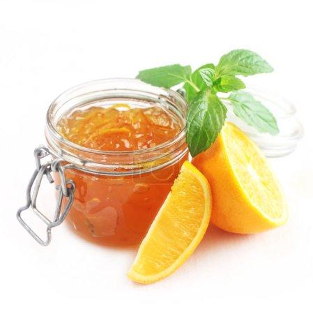 Photo pour Gros plan de pot de confiture orange avec menthe - image libre de droit