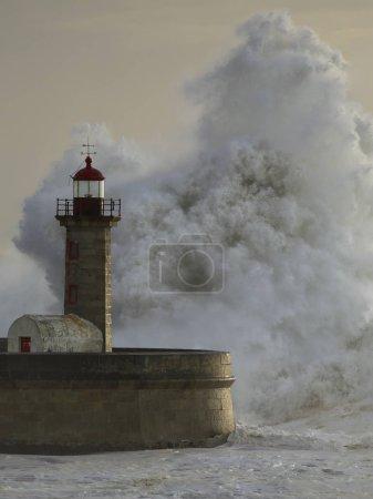 Big waves over lighthouse at sunset