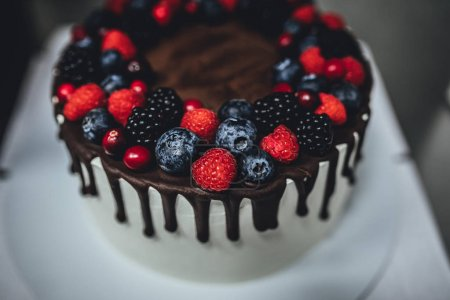 Photo for White cake with chocolate glaze and berrys, birthday cake in close up - Royalty Free Image
