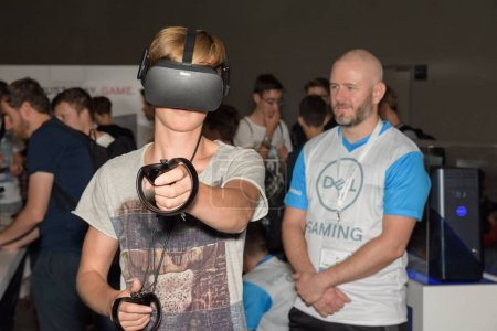 Photo for Cologne, Germany - August 24, 2017: A visitor is playing a virtual reality game with oculus rift + touch at the boot of Dell Gaming at Gamescom 2017. Gamescom is a trade fair for video games held annually in Cologne. - Royalty Free Image