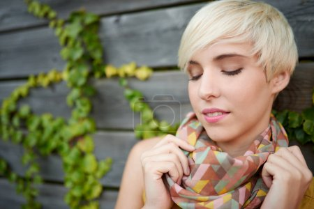 Beautiful short haired platinum blond woman standing against an ivy fence backdrop