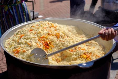 Cooking Uzbek pilaf dish in outdoor with beef meat...
