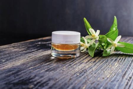Photo pour Huile essentielle de néroli (Citrus aurantium) dans un verre brun de fleurs blanches fraîches sur fond clair. Mise au point sélective. - image libre de droit