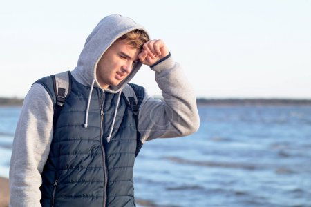 Photo pour Jeune homme souffrant d'un mal de tête sur l'arrière-plan de la baie en plein air. Beau mec tenant la tête sur le fond de la mer - image libre de droit