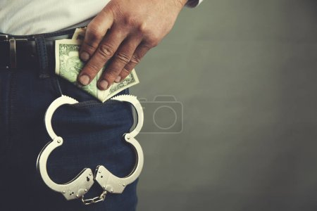 Photo for Man hand money with handcuffs in pocket - Royalty Free Image