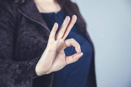 Foto de La mano de mujer buen signo en el fondo de la pared gris - Imagen libre de derechos