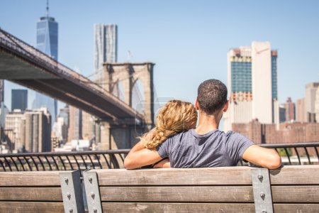 Photo pour Couple amoureux assis sur un banc et regardant Brooklyn Bridge et Manhattan skyline. Date romantique à New York - image libre de droit