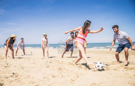 Friends playing soccer on beach