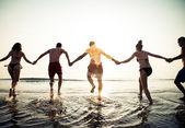Friends running into ocean at sunrise