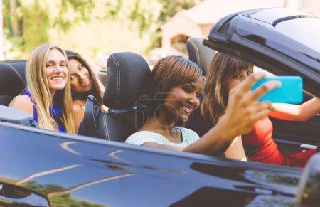 Girls taking selfie in convertible car