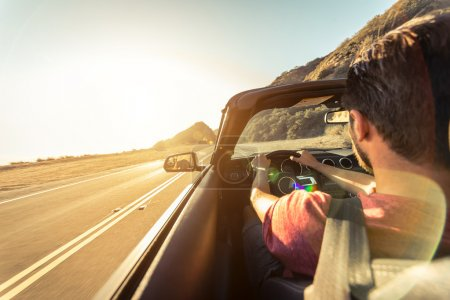 Photo pour Vue arrière de l'homme au volant d'une voiture décapotable de sport en Californie - image libre de droit
