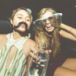 Beautiful girls with champagne in a convertible ca...