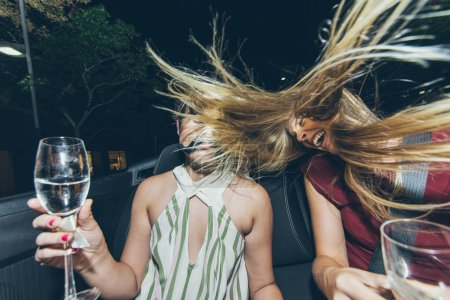 Girls with champagne in convertible car