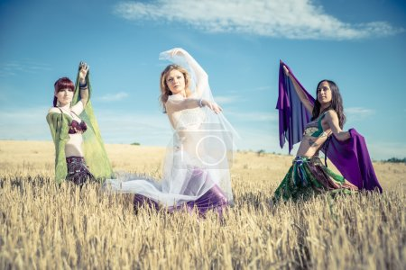 Belly dancers in wheat field