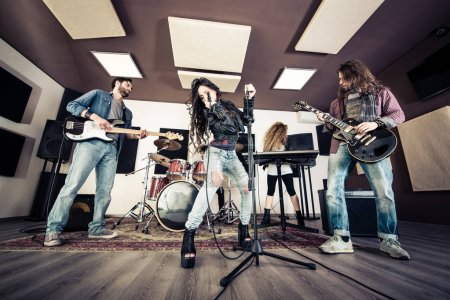 Photo pour Un groupe de rock enregistrant une chanson dans un studio de musique. Rock band jouant à l'intérieur - image libre de droit