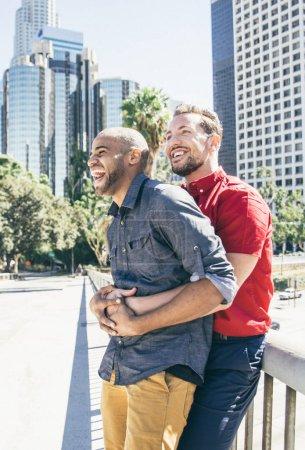 Photo pour Couple homosexuel à un rendez-vous romantique en plein air. Couple gay multiethnique amoureux datant et s'amusant - image libre de droit