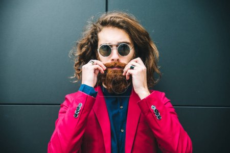 Photo for Fashion portrait of a young hipster man posing outdoors with a red formal suit - Royalty Free Image