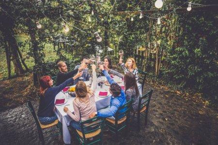 Photo pour Groupe d'amis assis à la table à l'extérieur. Les gens qui dînent dans le jardin - image libre de droit