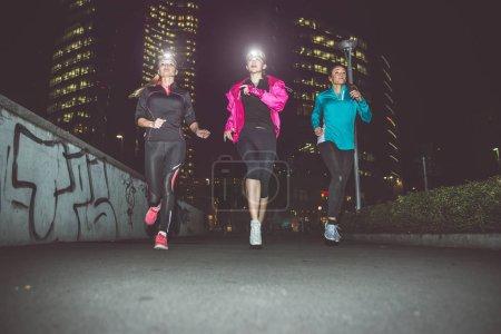 Three women running in the night in the city center