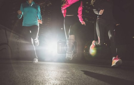 Photo for Three women running in the night in the city center - Royalty Free Image