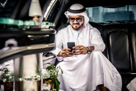 Photo pour Homme d'affaires arabe barbu en vêtements traditionnels utilisant un smartphone - image libre de droit
