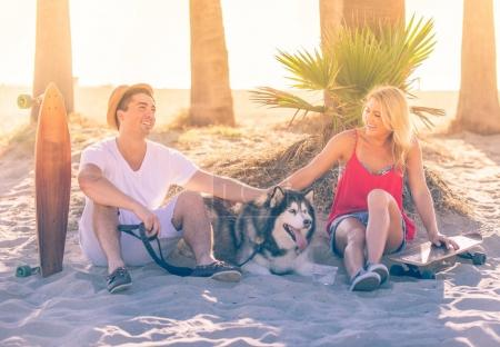 Couple with skateboards and husky