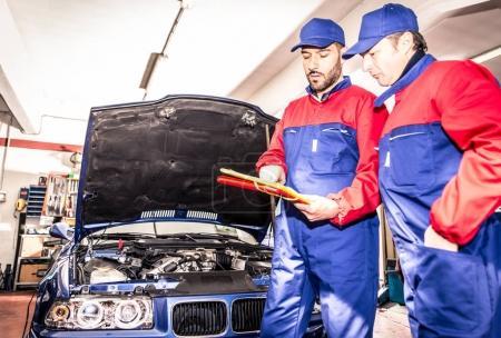 Mechanics working with car