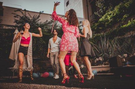Foto de Grupo multiétnico de amigos haciendo fiesta en un bar - alegres jóvenes divertirse y celebrar en un patio jardín con piscina - Imagen libre de derechos