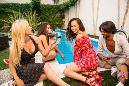 Photo for Multiethnic group of friends making party in a lounge bar - Cheerful young adults having fun and celebrating in a backyard garden with swimming pool - Royalty Free Image