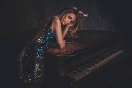 Beautiful woman with fancy elegant dress posing in the piano roo