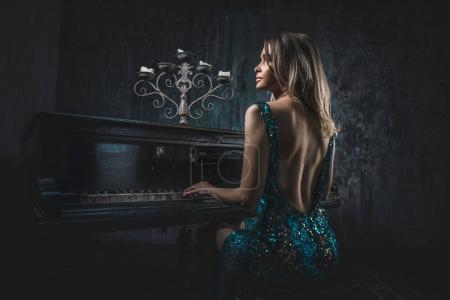 Foto de Hermosa mujer con disfraces elegantes posando en la sala de piano - Imagen libre de derechos