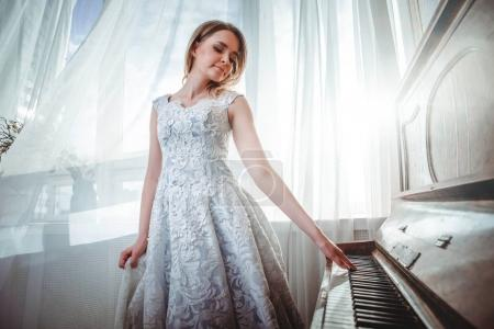Photo for Beautiful woman with fancy elegant dress posing in the piano room - Royalty Free Image